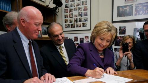 REFILE CAPTION ADDITONNew Hampshire Secretary of State Bill Gardner (L) looks on as U.S. Democratic presidential candidate Hillary Clinton signs her declaration of candidacy to appear on the New Hampshire primary election ballot in Concord, New Hampshire November 9, 2015. REUTERS/Brian Snyder
