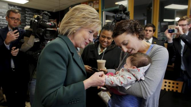 U.S. Democratic presidential candidate Hillary Clinton greets three month-old Hayley Bird and her mother Jody (R) during an off the schedule stop at the Bridge Cafe in Manchester, New Hampshire November 10, 2015.  REUTERS/Brian Snyder