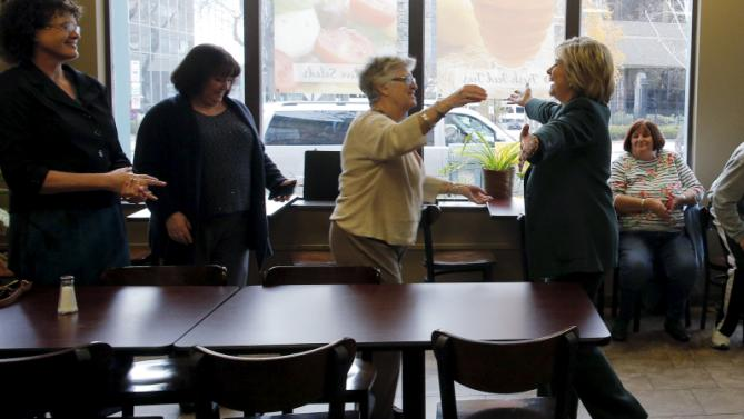 U.S. Democratic presidential candidate Hillary Clinton (R) is greeted as she makes an off the schedule stop at the Bridge Cafe in Manchester, New Hampshire November 10, 2015.  REUTERS/Brian Snyder