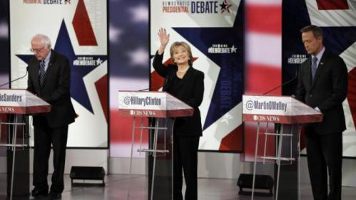 Hillary Rodham Clinton waves as Bernie Sanders, left, and Martin O'Malley prepare before a Democratic presidential primary debate, Saturday, Nov. 14, 2015, in Des Moines, Iowa. (AP Photo/Charlie Neibergall)