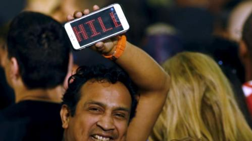 A man holds a cell phone with a message supporting Hillary Clinton who was set to speak at a Grassroots Organizing Event at Mountain View College in Dallas, Texas November 17, 2015.  REUTERS/Mike Stone
