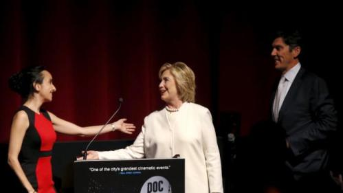 """Democratic U.S. presidential candidate Hillary Clinton greets DOC NYC Executive Director Raphaela Neihausen (L) as she arrives on stage to make remarks with AOL CEO Tim Armstrong (R) before the premiere of the documentary film """"Makers: Once And For All"""" at the DOC NYC documentary film festival in the Manhattan borough of New York City, November 19, 2015. """"Makers: Once And For All"""" tells the story of the 1995 Beijing Women's Conference and features commentary from the former U.S. First Lady and Secretary of State. REUTERS/Mike Segar"""