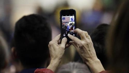 A woman takes a picture as Democratic presidential candidate Hillary Rodham Clinton speaks at Fisk University Friday, Nov. 20, 2015, in Nashville, Tenn. (AP Photo/Mark Humphrey)