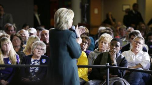 Audience members listens as Democratic presidential candidate Hillary Rodham Clinton speaks at a town hall meeting Sunday, Nov. 22, 2015, in Clinton, Iowa. (AP Photo/Charlie Neibergall)