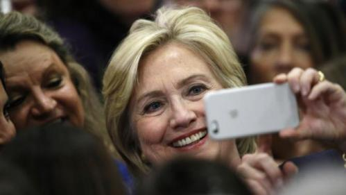 Democratic presidential candidate Hillary Rodham Clinton uses a supporter's mobile telephone to take a photograph after a rally Tuesday, Nov. 24, 2015, in a high school gymnasium in Denver. (AP Photo/David Zalubowski)