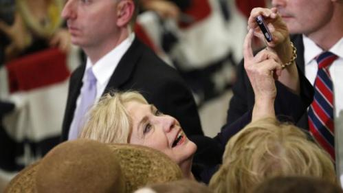 Democratic presidential candidate Hillary Rodham Clinton holds up a mobile telephone to take a photograph with a supporter while working a rope line following a rally Tuesday, Nov. 24, 2015, in a high school gymnasium in Denver. (AP Photo/David Zalubowski)
