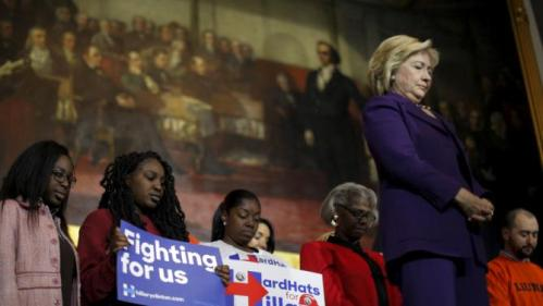 U.S. Democratic presidential candidate Hillary Clinton and audience members bow their heads for the victims of the mass shooting at a Colorado Planned Parenthood clinic, during a campaign rally at Faneuil Hall in Boston, Massachusetts November 29, 2015. REUTERS/Brian Snyder