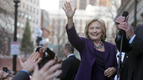 "Democratic presidential candidate Hillary Clinton, right, waves to people in a crowd before a rally at Faneuil Hall, Sunday, Nov. 29, 2015, in Boston. Clinton and Boston Mayor Marty Walsh attended the event held to launch ""Hard Hats for Hillary,"" a coalition to organize working families in construction, building, transportation, and other labor industries to support Clinton's agenda. (AP Photo/Steven Senne)"