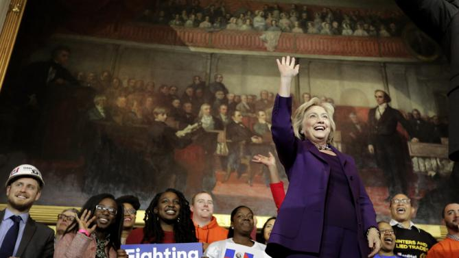 "Democratic presidential candidate Hillary Clinton, right, stands on stage as she greets people at the start of a rally at Faneuil Hall, Sunday, Nov. 29, 2015, in Boston. The event was held to launch ""Hard Hats for Hillary,"" a coalition created to organize people in industries and labor to support Clinton's agenda. (AP Photo/Steven Senne)"