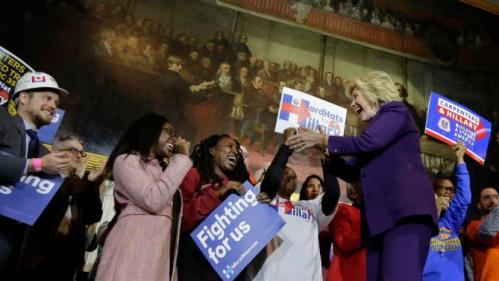 "Democratic presidential candidate Hillary Clinton, right, greets people on stage at the start of a rally at Faneuil Hall, Sunday, Nov. 29, 2015, in Boston. The event was held to launch ""Hard Hats for Hillary,"" a coalition created to organize people in industries and labor to support Clinton's agenda. (AP Photo/Steven Senne)"