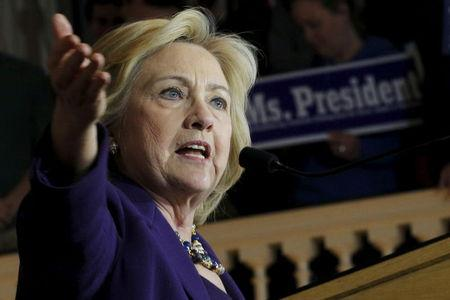 """U.S. Democratic presidential candidate Hillary Clinton speaks in front of an audience member holding a sign reading """"Ms. President"""" at a campaign rally with labor unions at Faneuil Hall in Boston, Massachusetts November 29, 2015. REUTERS/Brian Snyder"""