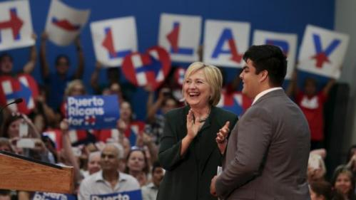 U.S. Democratic presidential candidate Hillary Clinton (C) walks on stage with John Quiroz, a former local college student before speaking at an election campaign event in Orlando, Florida December 2, 2015. REUTERS/Scott Audette