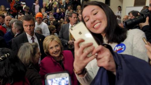 U.S. Democratic presidential candidate Hillary Clinton poses for a selfie with audience members at a campaign town hall meeting in Salem, New Hampshire December 8, 2015. REUTERS/Brian Snyder