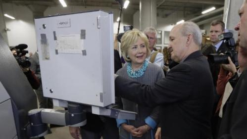 Democratic presidential candidate Hillary Clinton looks at a 3D printer as she tours the Cedar Valley TechWorks, Wednesday, Dec. 9, 2015, in Waterloo, Iowa. (AP Photo/Charlie Neibergall)