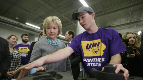 Democratic presidential candidate Hillary Clinton listens to Andrew Yersin, a junior at the University of Northern Iowa, as she tours the Cedar Valley TechWorks, Wednesday, Dec. 9, 2015, in Waterloo, Iowa. (AP Photo/Charlie Neibergall)