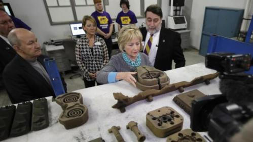 Democratic presidential candidate Hillary Clinton looks at some products as she tours the Cedar Valley TechWorks, Wednesday, Dec. 9, 2015, in Waterloo, Iowa. (AP Photo/Charlie Neibergall)