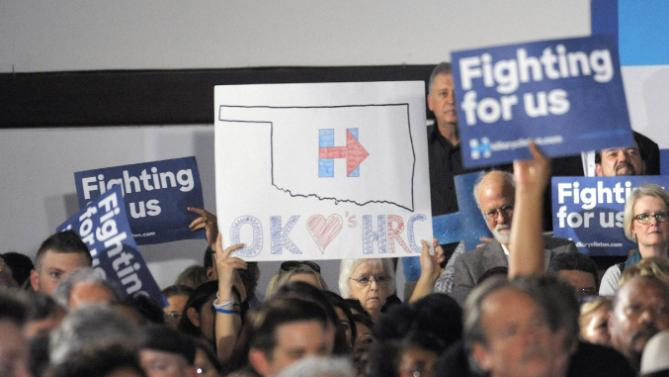 People hold up signs of support as Democratic presidential candidate Hillary Clinton speaks to a crowd during a campaign event held at the Oklahoma Jazz Hall of Fame in Tulsa, Okla., Friday, Dec. 11, 2015. (AP Photo/Brandi Simons)