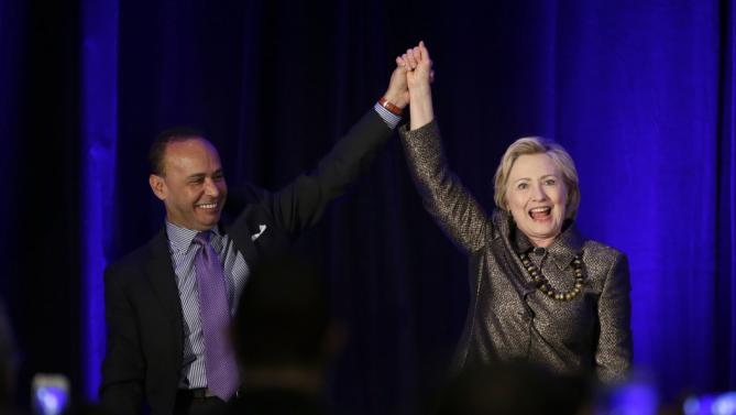 Democratic presidential candidate Hillary Clinton, right, holds hands with Rep. Luis Gutierrez, D-Ill., after speaking during the 2015 National Immigration Integration Conference in New York, Monday, Dec. 14, 2015. (AP Photo/Seth Wenig)