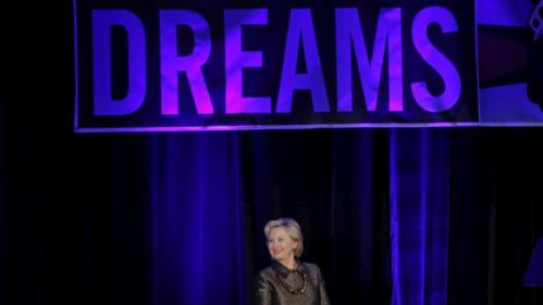 Democratic U.S. presidential candidate Hillary Clinton stands beneath a banner as she is introduced before addressing the 2015 National Immigrant Integration Conference in the Brooklyn borough of New York City, December 14, 2015. REUTERS/Mike Segar