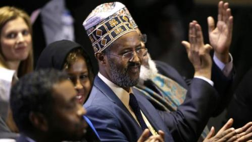 Imam Abdisalam Adam of Minneapolis, center, listens as Democratic presidential candidate Hillary Clinton speaks about her counterterrorism strategy during a speech at the University of Minnesota Tuesday, Dec. 15, 2015, in Minneapolis. (AP Photo/Charlie Neibergall)