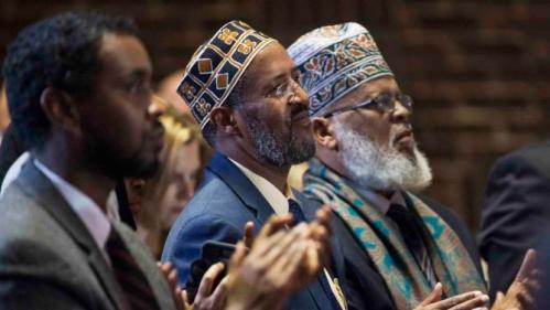 Minneapolis city council member Abdi Warsame (L) Imam Abdisalam Adam (C) from the Islamic Civic Society of America and Imam Saad Roble, President of the World Peace Organization applauds as Democratic presidential candidate Hillary Clinton talks about her counterterrorism strategy during a campaign stop in Minneapolis, Minnesota, December 15, 2015. REUTERS/Craig Lassig