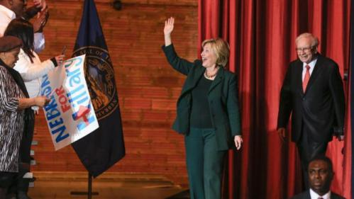 Democratic presidential candidate Hillary Clinton, accompanied by billionaire investor Warren Buffett, waves as she walks on stage at a Grassroots Organizing Event in Omaha, Neb., Wednesday, Dec. 16, 2015. (AP Photo/Nati Harnik)