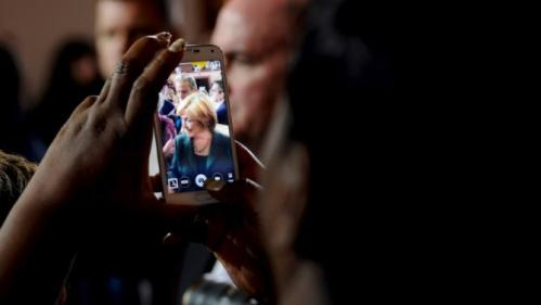 A supporter of U.S. Democratic presidential candidate Hillary Clinton takes a picture with her phone during a town hall event at Old Brick Church and Community Center in Iowa City, Iowa, December 16, 2015. REUTERS/Mark Kauzlarich