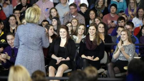 Students Kylea Tinnes, from left, Megan Adam and Abby Schulte listen as Democratic presidential candidate Hillary Clinton speaks during a town hall meeting at Keota High School, Tuesday, Dec. 22, 2015, in Keota, Iowa. (AP Photo/Charlie Neibergall)