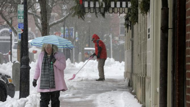 Julie Pugh, of Amesbury, Mass., left, holds an umbrella to shelter herself from snow Tuesday, Dec. 29, 2015 in Portsmouth, N.H. Pugh is visiting Portsmouth to attend a campaign event for Democratic presidential candidate Hillary Clinton. (AP Photo/Steven Senne)