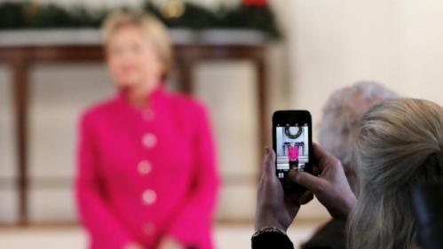 An audience member uses her mobile phone to photograph U.S. Democratic presidential candidate Hillary Clinton at a campaign town hall meeting at South Church in Portsmouth, New Hampshire December 29, 2015. REUTERS/Brian Snyder