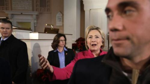 Democratic presidential candidate Hillary Clinton, behind right, stands near law enforcement officials while greeting people at the conclusion of a campaign event, Tuesday, Dec. 29, 2015, at South Church, in Portsmouth, N.H. (AP Photo/Steven Senne)