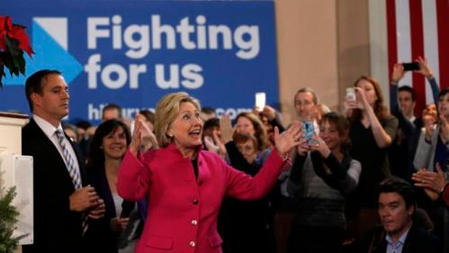 Democratic presidential candidate Hillary Clinton, center, raises her arms as she arrives at a campaign event Tuesday, Dec. 29, 2015, at South Church, in Portsmouth, N.H. (AP Photo/Steven Senne)