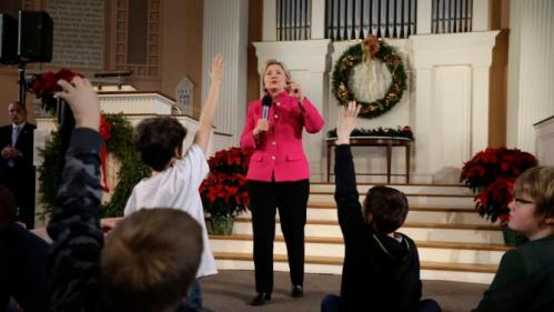 Democratic presidential candidate Hillary Clinton, center, takes questions as children raise their hands during a town hall style campaign event Tuesday, Dec. 29, 2015, at South Church, in Portsmouth, N.H. (AP Photo/Steven Senne)