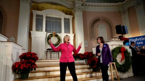 Democratic presidential candidate Hillary Clinton reacts to applause from the audience while standing with Brenda Bouchard, an Alzheimer's research advocate, during a town hall style campaign event, Tuesday, Dec. 29, 2015, at South Church in Portsmouth, N.H. (AP Photo/Steven Senne)