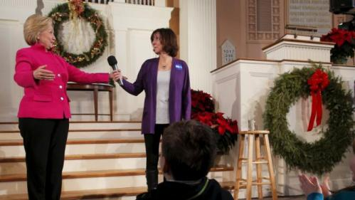 Brenda Bouchard offers the microphone to U.S. Democratic presidential candidate Hillary Clinton (L) as Bouchard introduced Clinton at a campaign town hall meeting at South Church in Portsmouth, New Hampshire December 29, 2015. Bouchard is an Alzheimer's research advocate who is supporting Clinton after questioning thirteen presidential candidates what they propose to address Alzheimer's disease. REUTERS/Brian Snyder