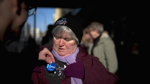 Iona Michaelis of West Point, Neb., gets a campaign sticker outside the Orpheum Theatre in Sioux City, Iowa, Tuesday, Jan. 5, 2016, where Democratic presidential candidate Hillary Clinton is scheduled to host a rally. (AP Photo/Jae C. Hong)