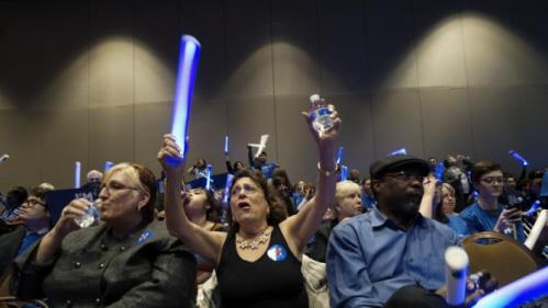 Supporters of U.S. Democratic presidential candidate Hillary Clinton wave flashing lights at a Democratic fundraising dinner featuring all three candidates in Las Vegas, Nevada January 6, 2016. Martin O'Malley and Bernie Sanders were also expected to attend. REUTERS/Rick Wilking