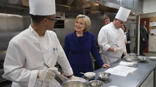 U.S. Democratic presidential candidate Hillary Clinton talks to students Mario Burrell (L) and Gary Brian Gonzalez making mayonnaise while touring the Culinary Academy of Las Vegas in North Las Vegas, Nevada January 6, 2016. REUTERS/Rick Wilking