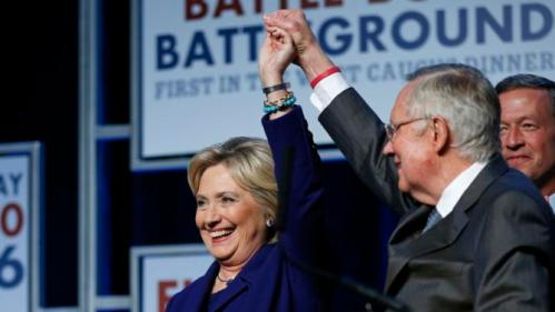 Senate Minority Leader Harry Reid, D-Nev., holds up the hand of Democratic presidential candidate Hillary Clinton on stage at the Battle Born Battleground First in the West Caucus Dinner, Wednesday, Jan. 6, 2016, in Las Vegas. Democratic presidential candidate, former Maryland Gov. Martin O'Malley is at right. (AP Photo/John Locher)
