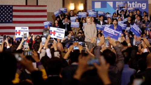 Democratic presidential candidate Hillary Clinton, middle, is welcomed by Rep. Judy Chu, D-Calif., at podium, before addressing Asian American and Pacific Islander supporters in San Gabriel, Calif., on Thursday, Jan. 7, 2016. (AP Photo/Damian Dovarganes)