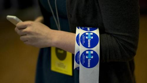 A volunteer carries a roll of campaign stickers for Democratic presidential candidate Hillary Clinton Monday, Jan. 11, 2016, in Waterloo, Iowa. (AP Photo/Jae C. Hong)