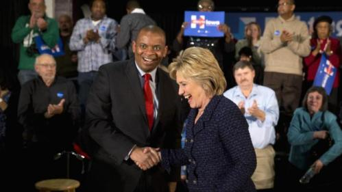 Democratic presidential candidate Hillary Clinton shares a laugh with Transportation Secretary Anthony Foxx during a rally, Monday, Jan. 11, 2016, in Waterloo, Iowa. (AP Photo/Jae C. Hong)
