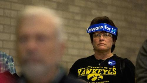 With a campaign sticker on her forehead, Robin Heath listens as Democratic presidential candidate Hillary Clinton speaks at a rally, Monday, Jan. 11, 2016, in Waterloo, Iowa. (AP Photo/Jae C. Hong)