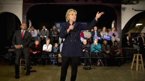 Transportation Secretary Anthony Foxx listens at left, as Democratic presidential candidate Hillary Clinton speaks at a campaign rally, Monday, Jan. 11, 2016, in Waterloo, Iowa. (AP Photo/Jae C. Hong)