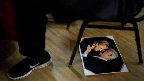 A photo of former President Bill Clinton and Democratic presidential candidate Hillary Clinton kissing is seen on the floor during a campaign rally with the candidate, Monday, Jan. 11, 2016, in Waterloo, Iowa. (AP Photo/Jae C. Hong)