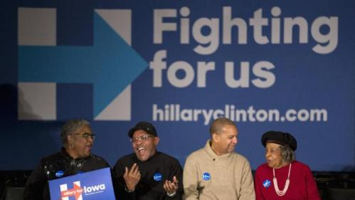 Supporters share a laugh and chat while waiting for Democratic presidential candidate Hillary Clinton at a campaign rally, Monday, Jan. 11, 2016, in Waterloo, Iowa. (AP Photo/Jae C. Hong)