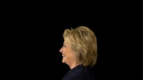 Democratic presidential candidate Hillary Clinton smiles while listening to Transportation Secretary Anthony Foxx speaks during a campaign rally, Monday, Jan. 11, 2016, in Waterloo, Iowa. (AP Photo/Jae C. Hong)