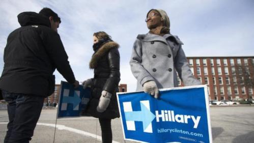 Volunteer Mishara Davis of Atlanta, Ga., right, holds a yard sign outside the Millyard Museum in Manchester, N.H., Tuesday, Jan. 12, 2016, before Chelsea Clinton, daughter of Democratic presidential candidate Hillary Clinton arrived to speak at a campaign stop in support of her mother. (AP Photo/John Minchillo)