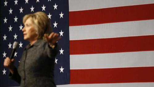 An American flag stands behind Democratic presidential candidate Hillary Clinton as she speaks during a campaign event at Iowa State University in Ames, Iowa, Tuesday, Jan. 12, 2016. (AP Photo/Patrick Semansky)