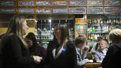 Chelsea Clinton, left, shakes hands with a supporter as customers sit at the bar during a campaign stop for her mother Democratic presidential candidate Hillary Clinton at Portsmouth Brewery, Tuesday, Jan. 12, 2016, in Portsmouth, N.H. (AP Photo/John Minchillo)